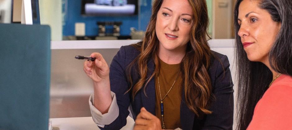 Två kvinnor på jobbet som diskuterar framför en laptop.